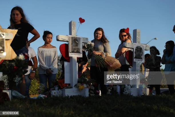 People visit a makeshift memorial setup in front of Marjory Stoneman Douglas High School on February 18 2018 in Parkland Florida Police arrested and...
