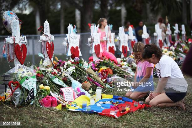 People visit a makeshift memorial setup in front of Marjory Stoneman Douglas High School on February 19 2018 in Parkland Florida Police arrested and...