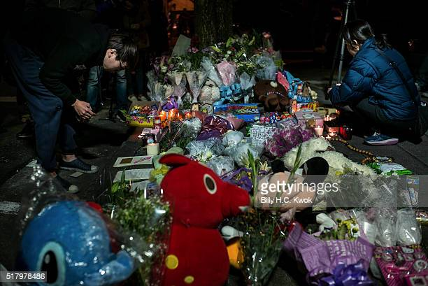 People visit a makeshift memorial where a girl was found decapitated by a knifewielding assailant outside a subway station on March 28 2016 in Taipei...