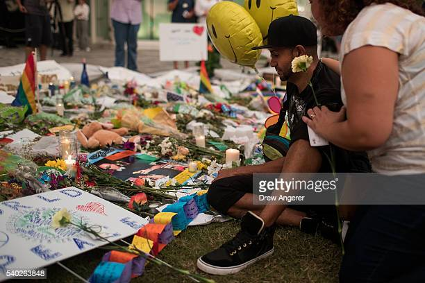 People visit a memorial for the victims of the Pulse Nightclub shooting at the Dr Phillips Center for Performing Arts June 14 2016 in Orlando Florida...