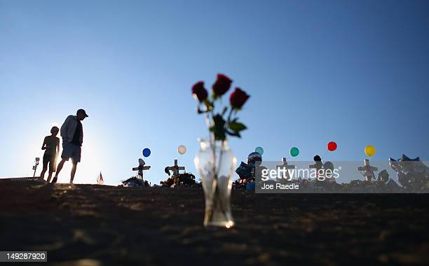People visit a memorial setup across the street from the Century 16 movie theatre on July 26 2012 in Aurora Colorado Twentyfouryearold James Holmes...