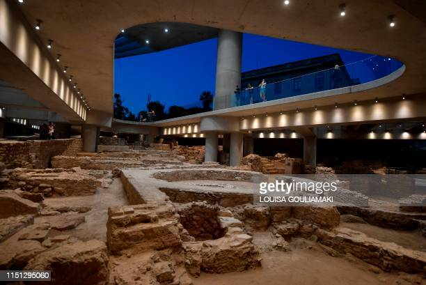 People visit a new section housing the remains of an ancient Athens neighbourhood beneath the Acropolis museum in Athens, on its opening day on June...