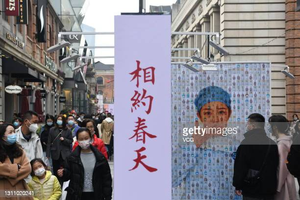 People visit a photography exhibition on Wuhan's fight against COVID-19 at a pedestrian street on April 4, 2021 in Wuhan, Hubei Province of China.