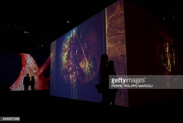 People visit a video installation on Dutch painter Hieronymus Bosch's masterpiece The Garden of Earthly Delights at El Prado museum in Madrid on July...