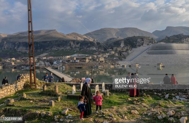 People visit abandoned houses of the ancient city of Hasankeyf which will soon be under water as part of a controversial dam project, on February 24,...