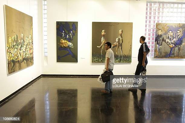 People visit an exhibition by the Norwegian artist Haakon Gullvaag entitled Terra Sancta on display at the French Cultural center in Damascus on...