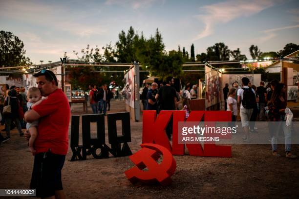 People visit an exibition for the 100 years anniversary of the Greek Communist party during an annual festival of the party's youth wing in Athens on...
