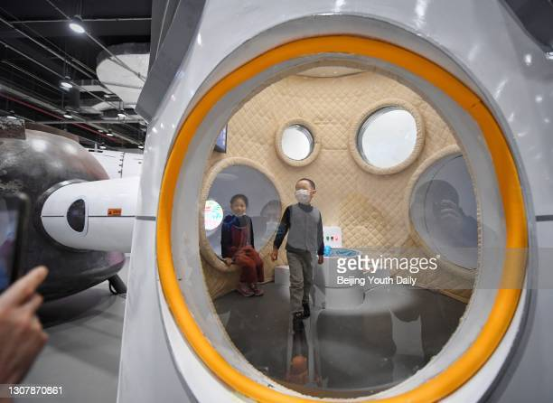 People visit an interactive technological exhibition on the development of China's manned space program at China Science and Technology Museum on...