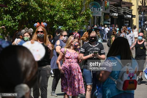 People visit Downtown Disney in Anaheim, California on July 9 the first day the outdoor shopping and dining complex has been open to the public since...