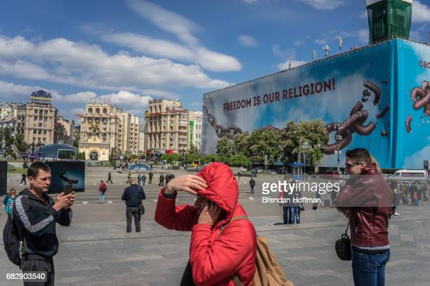 People visit Independence Square where a large banner reading Freedom is Our Religion was hung on the former Trade Unions building which burned...