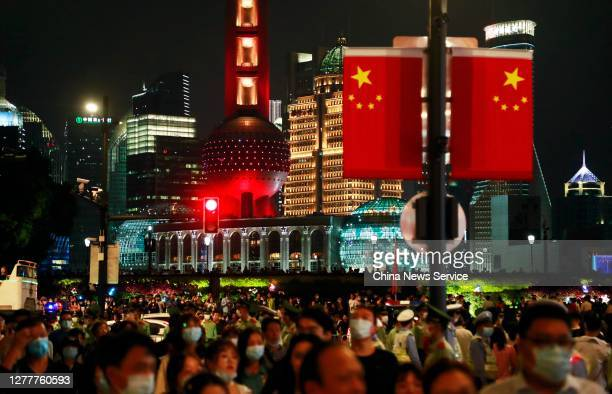 People visit Nanjing Road pedestrian street decorated with Chinese flags to mark upcoming Chinese National Day on September 30, 2020 in Shanghai,...