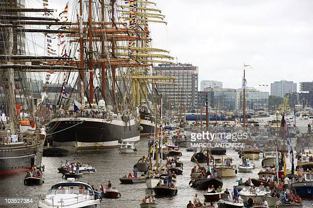 People visit ships mooring in the eastern harbour of the Amsterdam on August 20 2010 as they attend the maritime manifestation SAIL Amsterdam held...