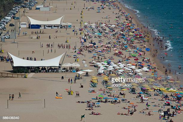 People visit the beach in the Catalonian coastal city of Calella de Mar on August 6 2016 / AFP / JOSEP LAGO