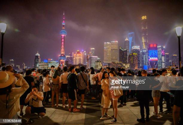People visit the Bund along the Huangpu River as the skyline of the city in the Pudong district is seen on August 29, 2020 in Shanghai, China.