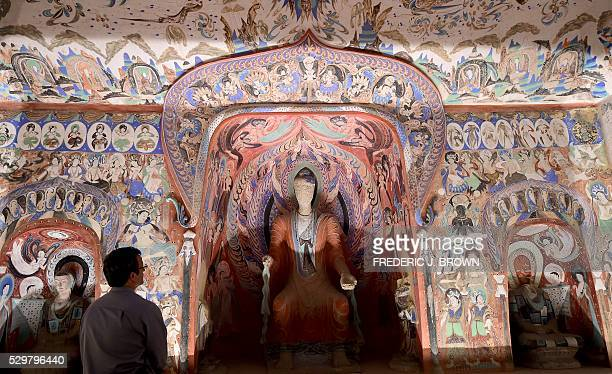 """People visit the """"Cave Temples of Dunhuang: Buddhist Art on the Silk Road"""" exhibit at the Getty Center in Los Angeles on May 9 viewing a full-scale,..."""