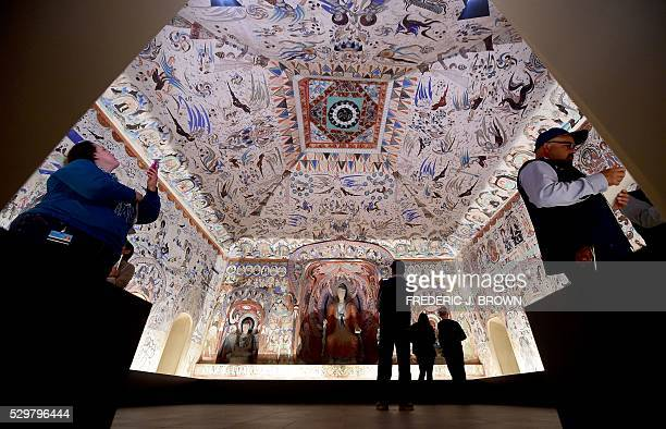 People visit the 'Cave Temples of Dunhuang Buddhist Art on the Silk Road' exhibit at the Getty Center in Los Angeles on May 9 viewing a fullscale...