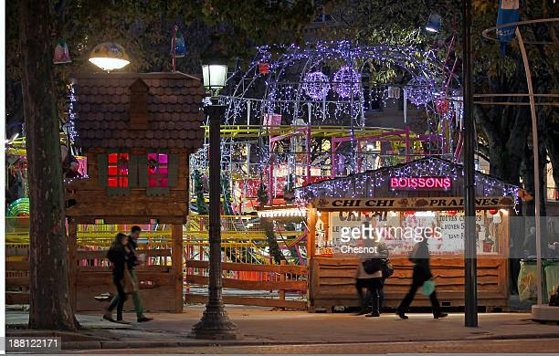 People visit the Christmas market on the ChampsElysees avenue on November 15 2013 in Paris France For the 5th year a Christmas market is located on...