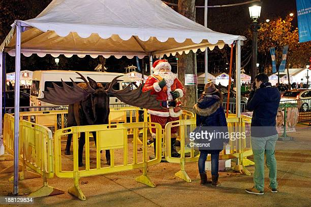 People visit the Christmas market on the ChampsElysees on November 15 2013 in Paris France In its fifth year a Christmas market located on the...