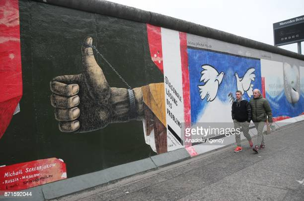 People visit the East Side Gallery on the 27th anniversary of the fall of the Berlin Wall in Berlin Germany on November 5 2017 Brandenburg Gate is an...