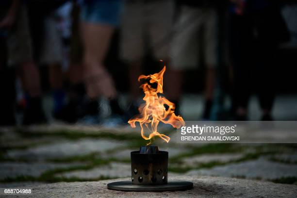 People visit the Eternal Flame at the grave of assassinated former US President John F Kennedy near the 100th anniversary of his birth at Arlington...