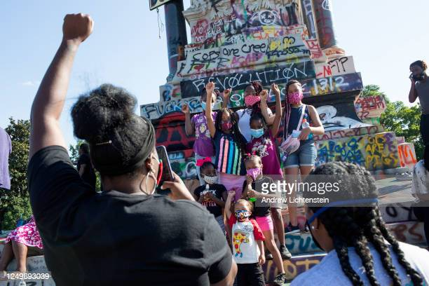 People visit the graffiticovered statue of Confederate General Robert E Lee on June 14 2020 at Monument Avenue in Richmond Virginia The killing of...