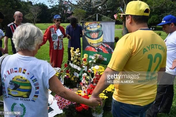 People visit the grave of Brazilian's F1 driver Ayrton Senna in Sao Paulo Brazil on May 1 paying tribute to the 25th anniversary of his death during...
