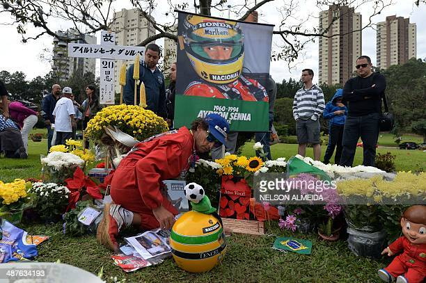 People visit the grave of Brazilian's F1 driver Ayrton Senna in Sao Paulo Brazil on May 1 paying tribute to the 20th anniversary of his death during...