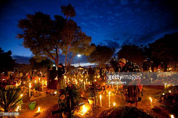 People visit the grave of relatives with flowers and candles during of the Day of the Dead celebrations on November 1 2012 in Oaxaca Mexico