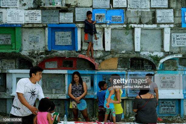 People visit the graves of their relatives in a cemetery during the commemoration of All Saints' Day in Manila on November 1 2018 in Manila...