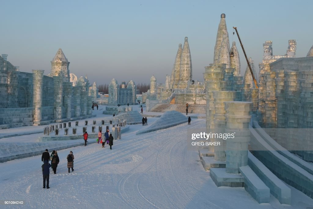 People visit the Harbin Ice and Snow World, part of the annual Harbin Ice and Snow Sculpture Festival in Harbin in China's northeast Heilongjiang province on January 4, 2018. The festival, which attracts hundreds of thousands of visitors annually, officially opens on January 5. /