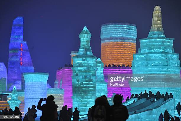 People visit the ice sculptures illuminated by coloured lights at Harbin ice and snow world to celebrate the new year in Harbin city of China on...