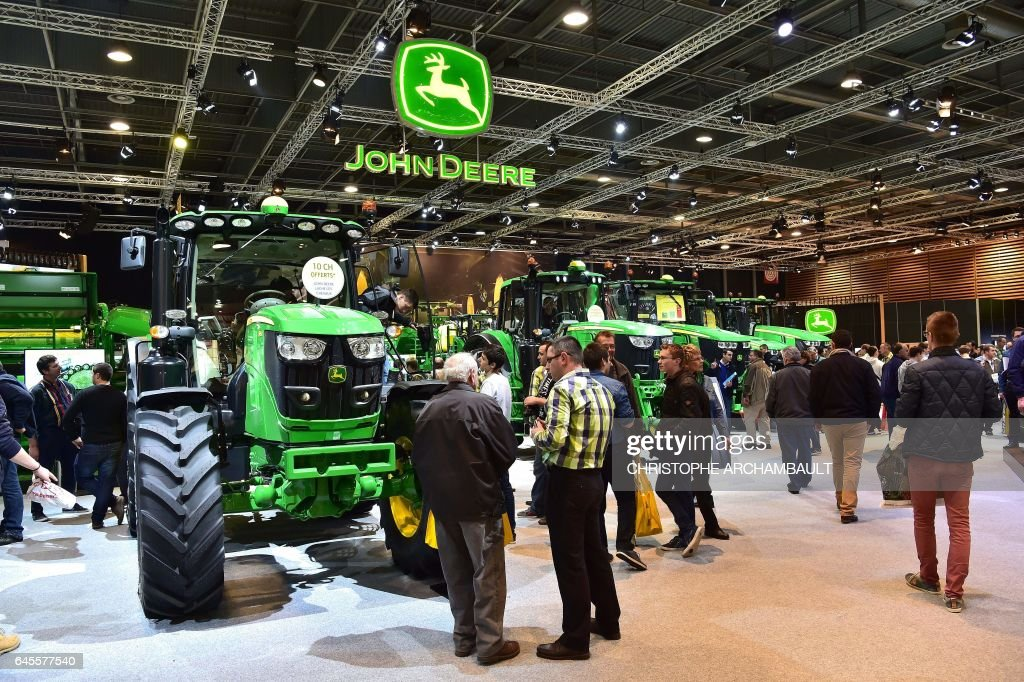 People visit the John Deere tractors stand during the SIMA, Paris International agribusiness show at the Parc des Expositions Paris Nord in Villepinte on February 26, 2017. / AFP / CHRISTOPHE