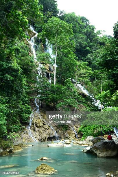 People visit the Lapopu waterfall in West Sumba in East Nusa Tenggara Province on October 21 2017 / AFP PHOTO / SONNY TUMBELAKA