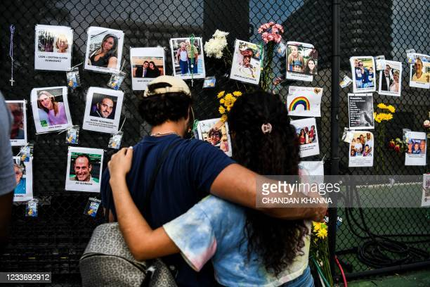 People visit the makeshift memorial for the victims of the building collapse, near the site of the accident in Surfside, Florida, north of Miami...