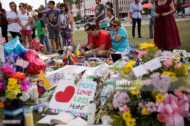 People visit the makeshift memorial for the victims of the Pulse Nightclub shooting lay at a makeshift memorial June 14 2016 in Orlando Florida The...