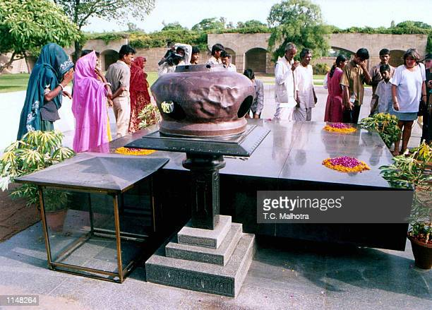 People visit the mausoleum of Mahatma Gandhi one of the mausoleum's corners was broken with a heavy hammer by a man on July 241998 in New Delhi India...