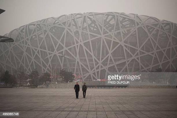 People visit the National Bird Nest stadium on a polluted day in Beijing on December 1 2015 China has ordered thousands of factories to shut as it...