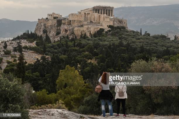 People visit the Pnyx Hill in Athens overlooking the ancient Acropolis on May 29, 2020 as Greece eases lockdown measures taken to curb the spread of...