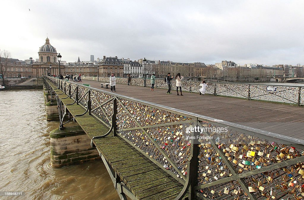 People visit the Pont des Arts on January 4, 2013 in Paris, France. The nine-arch metallic footbridge completed in 1804 is one of the most romantic places of the capital where people visit it to attach love padlocks illustrated with their initials or messages of love, before throwing the key into the River Seine. The bridge is also a meeting place for artists who find inspiration from the surrounding views of the city.