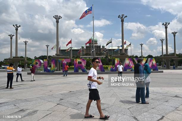 People visit the Putra Square in Putrajaya where Malaysia's Prime Minister office is seen in the background on February 21 2019