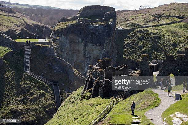 People visit the ruins of Tintagel Castle in Tintagel on April 28 2016 in Cornwall England The English Heritage managed site and the nearby town have...