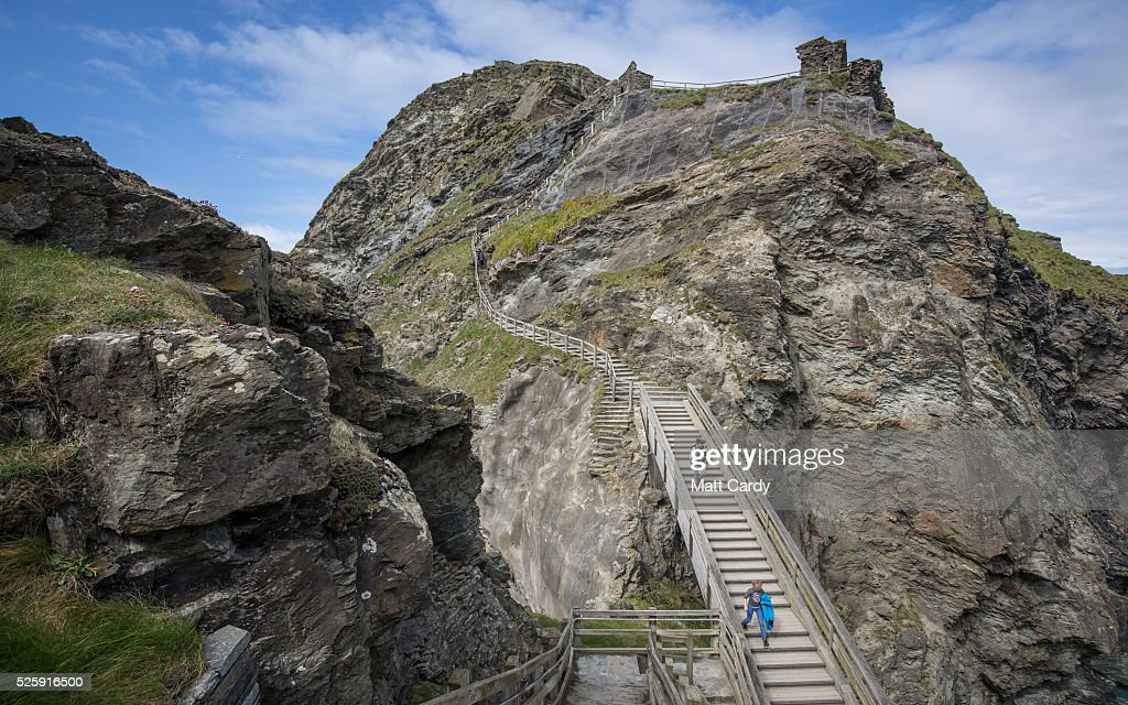 People visit the ruins of Tintagel Castle in Tintagel on April 28, 2016 in Cornwall, England. The English Heritage managed site and the nearby town have long been associated with the legend of King Arthur and continue to attract large visitor numbers. However, efforts by English Heritage to update the visitor experience with the Gallos sculpture, along with a rock carving of Merlin's face, which English Heritage say are inspired by the legend of King Arthur and Tintagel Castles royal past, have met with criticism from some Cornish nationalists and historians.