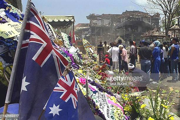 People visit the site of the 12 October bombing as two Australian flags sit amongst flowers in Kuta near Denpasar 20 October 2002 The number of...