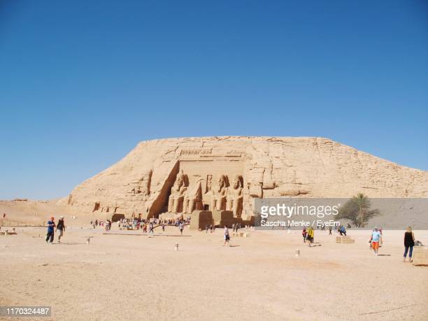 people visiting old ruin against clear blue sky during sunny day - abu simbel stock pictures, royalty-free photos & images