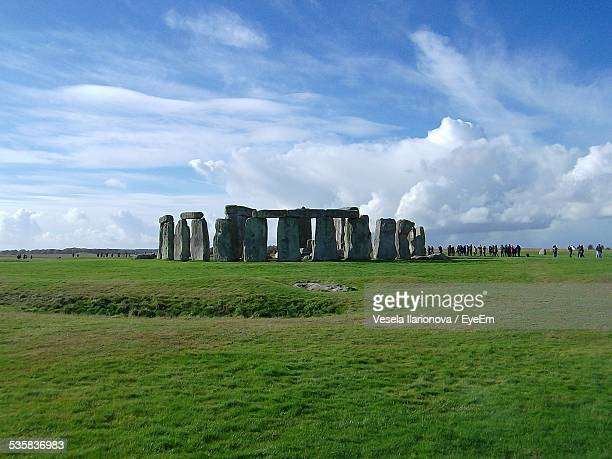 People Visiting Stonehenge Against Cloudy Sky
