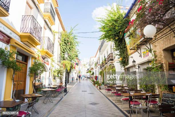 People visiting the beautiful narrow streets in the south of Spain with white houses and vegetation with flowers during trip in the sunny Andalucia.