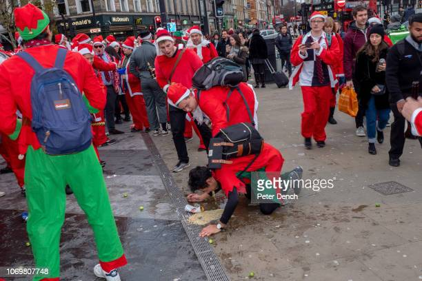 People vomit in the street as they drink and take part in the SantaCon 2018 on December 8 2018 in London England SantaCon is an annual pub crawl...