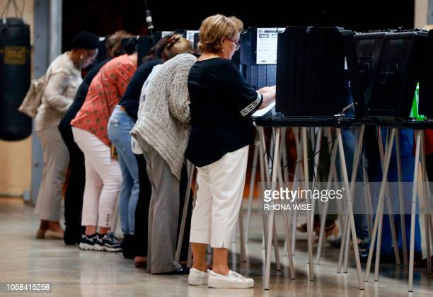 People vote at a polling station in Miami, Florida, on November 6, 2018. - Americans vote today in critical midterm elections that mark the first...