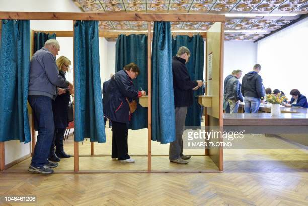 People vote at a polling station in Ogre Latvia during general elections on October 6 2018