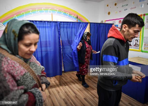 People vote at a polling station in Sindrilita during presidential elections on November 24, 2019. - Romanians voted in the second round of...